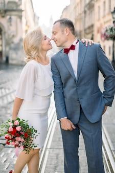 愛するカップル、スーツと蝶ネクタイの50歳のハンサムな男性の肖像画をクローズアップ、旧市街の背景に、花の花束と白いドレスで彼のきれいな女性と一緒に立っています