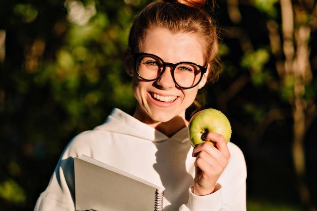 丸いメガネで壮大な白人の女の子のクローズアップの肖像画。