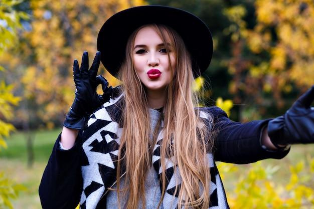 Макро портрет великолепной дамы в черной шляпе, дурачящейся во время осенней фотосессии. смешная барышня в элегантных перчатках проводит время в парке в сентябрьский день.
