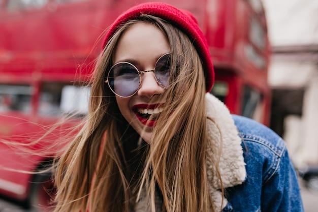 通りで笑っている黒髪の壮大な若い女性のクローズアップの肖像画。都会でのんびりしながら春の週末に楽しんでいるデニムジャケットの感情的な女の子の屋外ショット。
