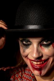 Крупным планом портрет макияжа женщина клоун, глядя на камеру