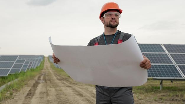 Закройте вверх по портрету мужского электрического работника в защитном шлеме, изучая дизайн бумажного плана солнечной электростанции. чистая энергия. промышленность. концепция зеленой энергии.