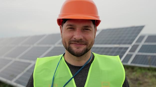 Закройте вверх по портрету мужского электрического работника в защитном шлеме, стоящем панелью солнечных батарей. производство чистой энергии. зеленая энергия. экологическая солнечная ферма.