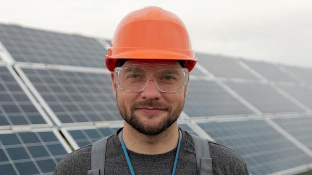 태양 전지 패널 근처에 서 있는 보호 헬멧에 남성 전기 작업자의 초상화를 닫습니다. 청정 에너지 생산. 친환경 에너지. 생태 태양광 발전소.