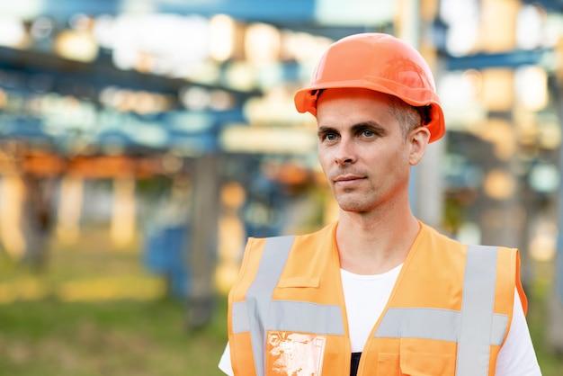 유니폼을 입고 헬멧을 쓴 남성 엔지니어의 초상화를 닫고 야외에서 서 있는 남자 작업자