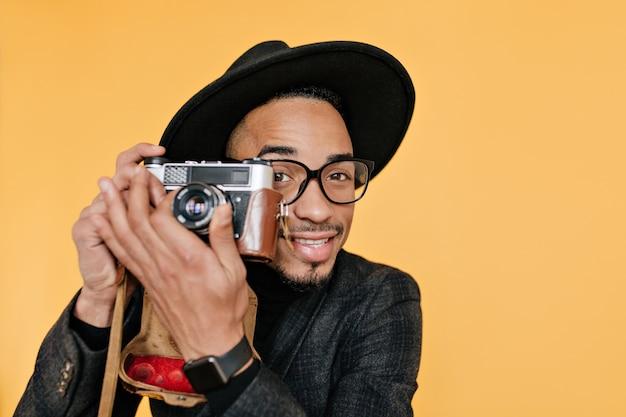 茶色の目と黒い肌を持つ男性写真家のクローズアップの肖像画。カメラで作業しているアフリカ人の笑顔。