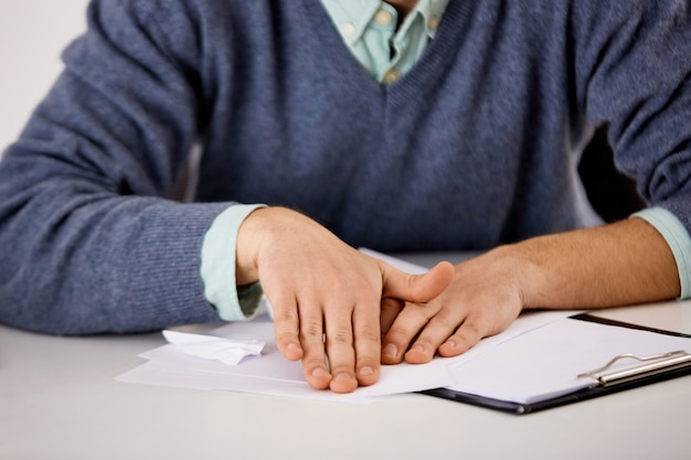 Крупным планом портрет человека руками, офисный работник делает оригами из документов, скучно на работе