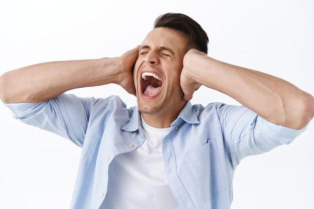 Крупным планом портрет человека, кричащего и качающего головой в отрицании, закрывающего глаза и закрывающего уши руками, испытывающего эмоциональное выгорание на работе, испытывающего огромное давление и стресса, стоящего у депрессивной белой стены