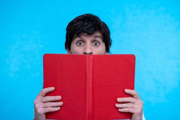 明るい青色の表面で本のタスクの読書の後ろに隠れている賢い賢い怖い男のクローズアップの肖像画