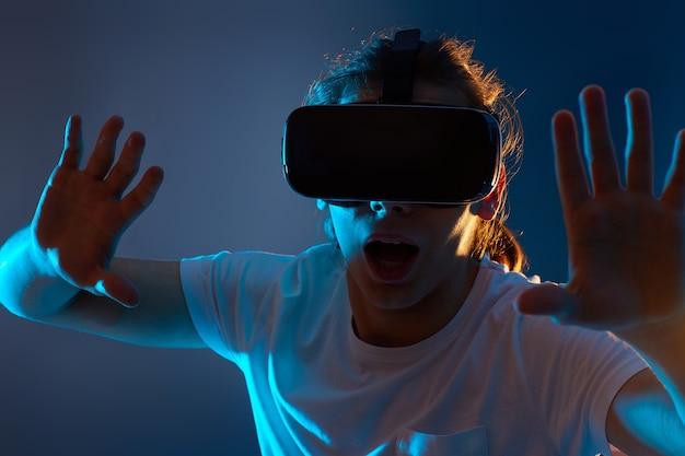 Крупным планом портрет человека, использующего очки виртуальной реальности на синем фоне. неоновый свет.