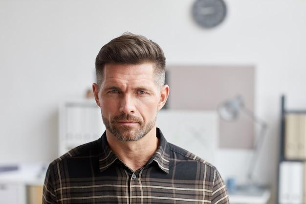 Крупным планом портрет зрелого бородатого мужчины, стоя в офисе архитекторов