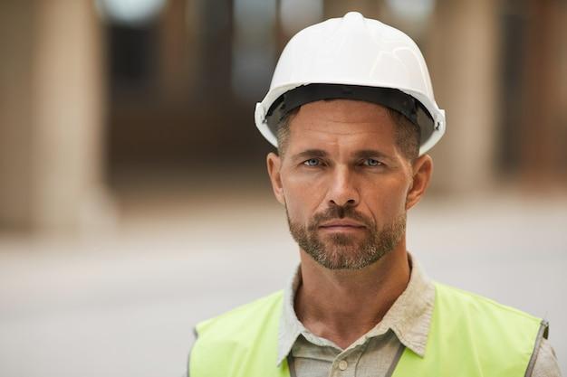 안전모를 착용하고 건설 현장에 서있는 동안 성숙한 건설 노동자의 초상화를 닫습니다.
