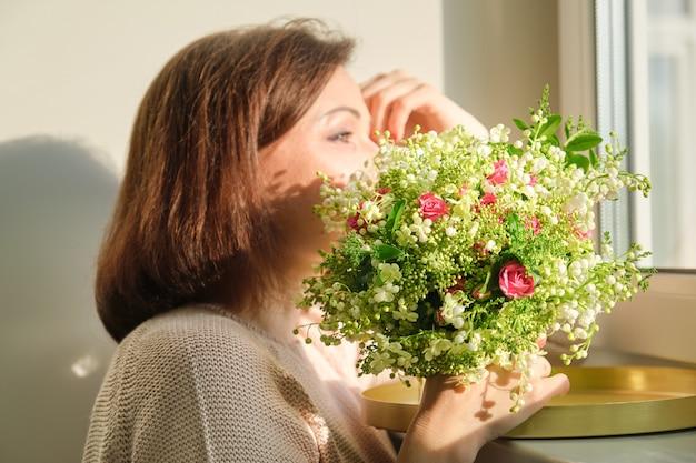 꽃의 부케와 성숙한 여자의 초상화를 닫습니다