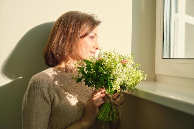 Крупным планом портрет зрелой женщины с букетом цветов