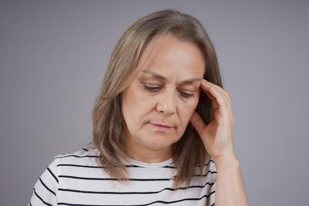 頭痛に苦しんでいる中年女性の肖像画をクローズアップ