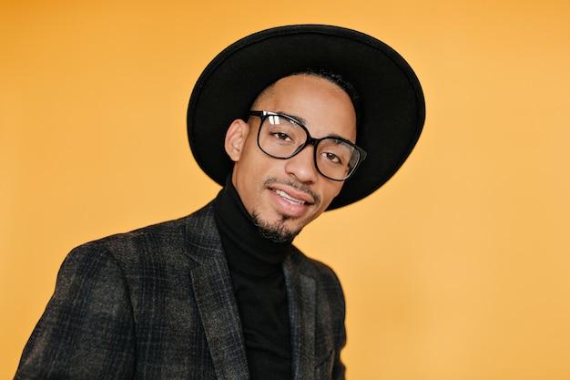 黒い帽子のムラート男性モデルのクローズアップの肖像画。茶色の肌を持つ陽気な若い男の屋内写真。