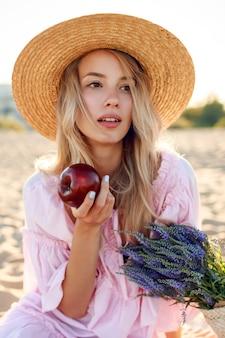 海の近くで週末を楽しんでいる麦わら帽子の自然な白人の女の子の肖像画を閉じます。果物でポーズをとる。ストローバッグのラベンダーの花束。