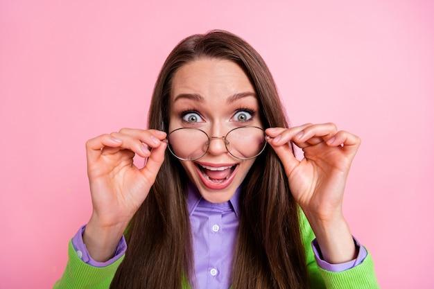 Крупным планом портрет красивой удивленной веселой сумасшедшей безумно счастливой девушки-компьютерщика, трогающей спецификации, крутая реакция на новости, изолированные на розовом фоне пастельных тонов