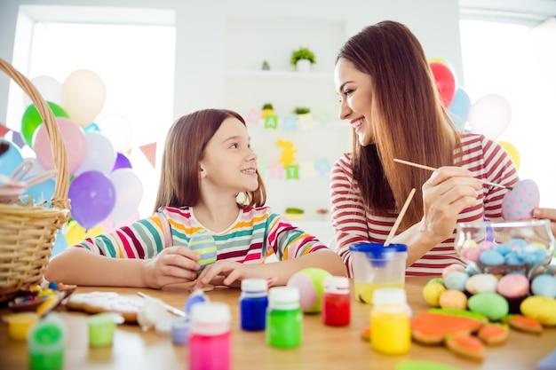 素敵な魅力的な陽気な陽気な女の子のクローズアップの肖像画小さな小さな娘がお祭りのお祝いの装飾的な要素を作成します4月の日は屋内の白い光のインテリアルームの家で時間を過ごします