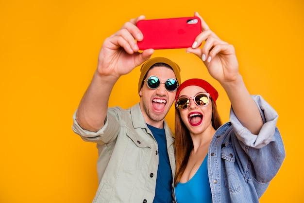 明るい鮮やかな輝き鮮やかな黄色の背景の上に分離された楽しい旅行旅行旅行夏を持って自分撮りを作る素敵な魅力的な陽気な嬉しいカップルのクローズアップの肖像画