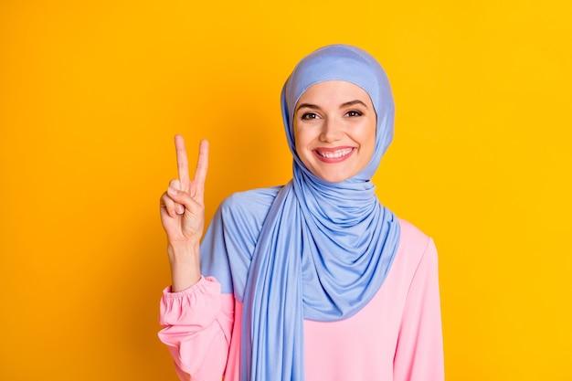 밝은 노란색 배경 위에 격리된 v 기호를 보여주는 멋지고 쾌활한 이슬람 여성의 클로즈업 초상화