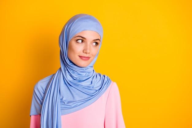 밝은 노란색 배경 위에 고립된 채 히잡을 쓰고 있는 멋지고 쾌활한 똑똑한 이슬람교도의 클로즈업 초상화