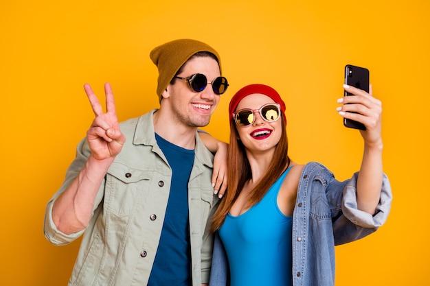 素敵な魅力的な嬉しい陽気なカップルの友人の友情のクローズアップの肖像画は、明るい鮮やかな輝きの鮮やかな黄色の背景の上に分離されたvサインを示す自分撮りを示しています