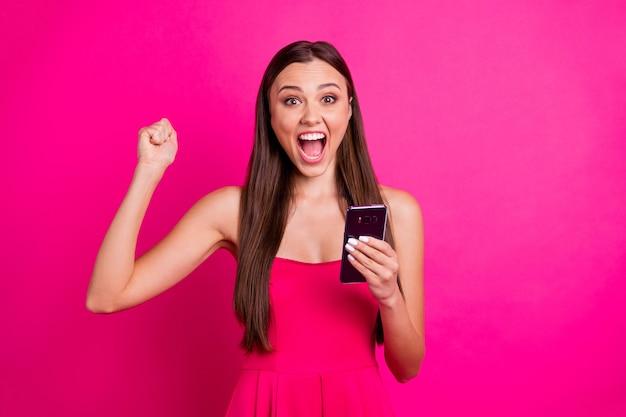 Макро портрет красивой привлекательной прекрасной очаровательной веселой веселой длинноволосой девушки, использующей сотовый, празднует sms-сообщение о зарплате, изолированное на ярком ярком блеске ярком розовом цветном фоне фуксии