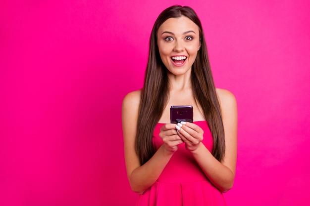 Портрет крупным планом красивой привлекательной милой очаровательной веселой веселой увлеченной длинноволосой девушки, ищущей веб-серфинг, изолированной на ярком ярком сиянии яркого розового цвета фуксии