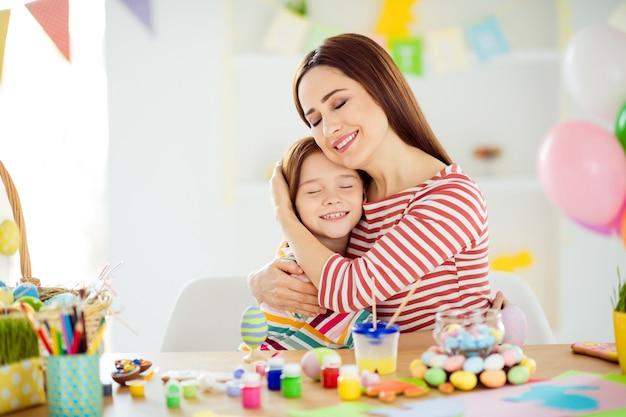 素敵な魅力的な素敵な優しい優しい甘い陽気な陽気な女の子のクローズアップの肖像画小さな小さな娘が4月を白い光の室内の部屋の家に抱き締めて手工芸品を作成します
