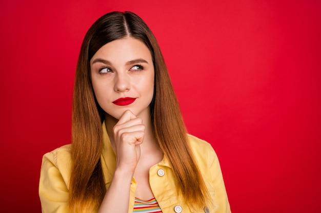 素敵な魅力的な素敵なかなりずる賢い懐疑的な心の創造的な赤い髪の少女のクローズアップの肖像画は、明るい鮮やかな輝きの鮮やかな赤い色の背景に分離された手がかりを推測するニュースを考えすぎています