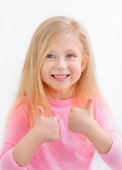 Крупным планом портрет красивой милой веселой маленькой девочки, показывая двойные пальцы вверх