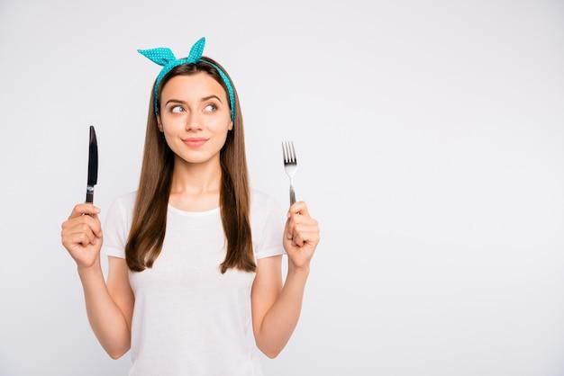 分離された健康的な有機ダイエットの日を選択するフォークナイフを手に持っている素敵な素敵な女の子のクローズアップの肖像画