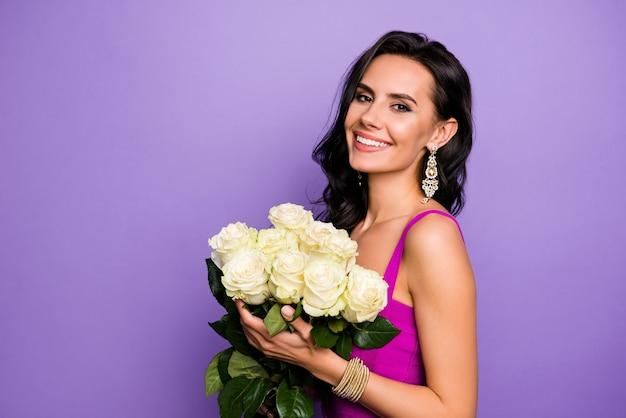分離された新鮮な白いバラを手に持っている素敵なリッチでファッショナブルなウェーブのかかった髪の女性のクローズアップの肖像画