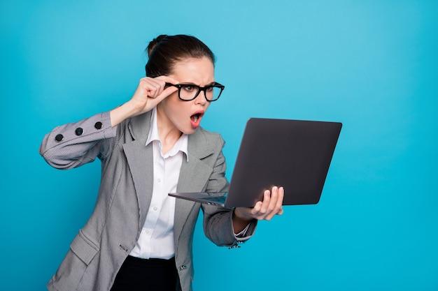 밝은 파란색 배경에서 격리된 화면을 보고 있는 노트북을 들고 있는 걱정스러운 여성 괴짜 it 전문가의 클로즈업 초상화