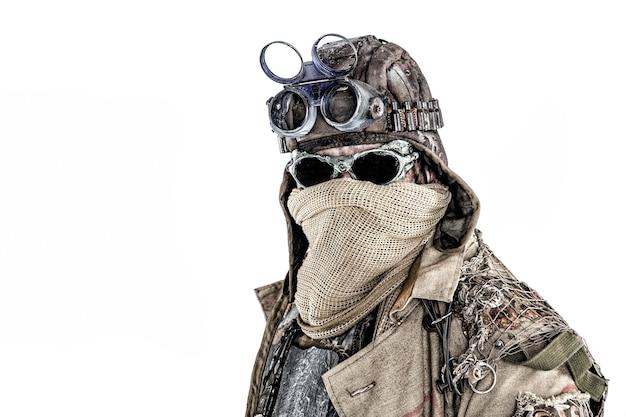 Крупным планом портрет пережившего ядерный судный день, мародера постапокалиптического мира с лицом, спрятанным за вретищевой маской и солнцезащитными очками, в рваных лохмотьях и барахле, изолированном на белом фоне с copyspace
