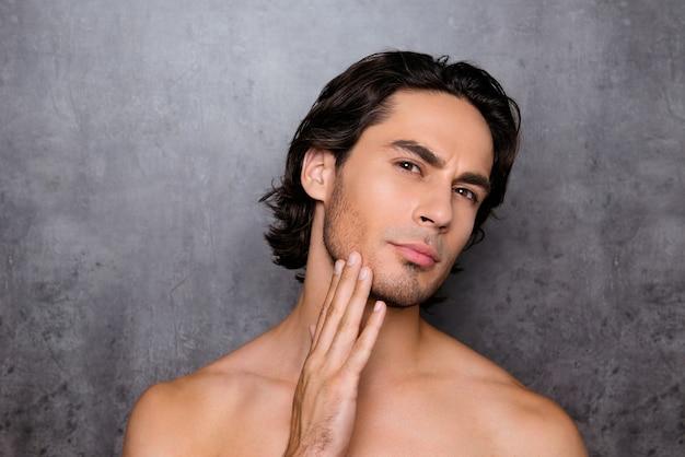 彼のあごに触れている裸の男の肖像画をクローズアップ