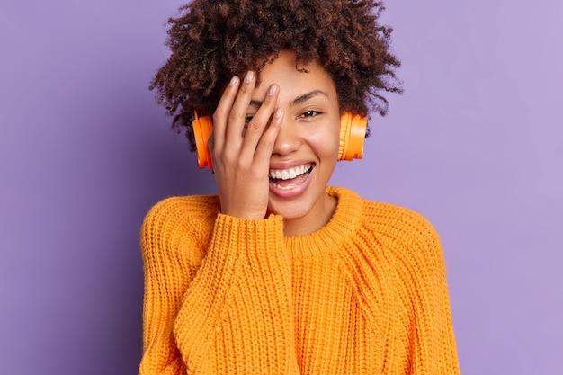 大喜びの浅黒い肌の女性のクローズアップの肖像画は、顔に手を保ち、のんびりと笑顔で、カジュアルな服装のヘッドフォンでお気に入りの音楽を聴き、ポジティブな感情を表現します