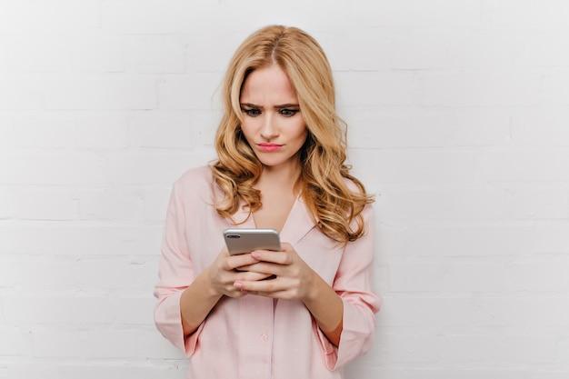 電話メッセージを読んで淡いブロンドの女性のクローズアップの肖像画。スマートフォンの画面を見ている綿のナイトスーツで不幸な巻き毛の女性の屋内写真。