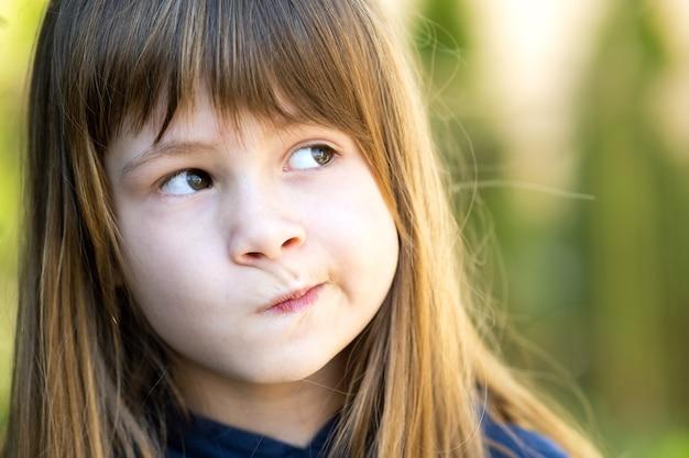 Закройте вверх по портрету задумчивой милой девушки ребенка брюнет в парке.