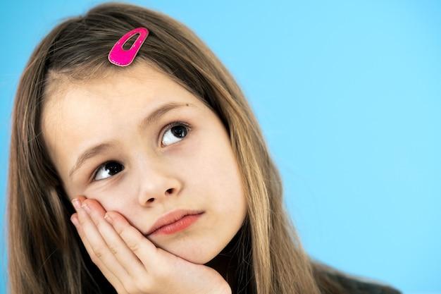 파란색 벽에 분홍색 머리핀을 꽂은 잠겨있는 귀여운 소녀의 초상화를 닫습니다.