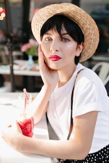 Крупным планом портрет задумчивой девушки с серыми глазами и красными губами, отдыхающей в кафе со стаканом ледяного напитка