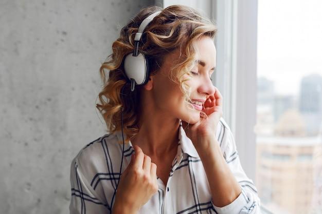 Крупным планом портрет задумчивой улыбающейся женщины, слушающей музыку в наушниках, позирует возле окна. современный городской интерьер.