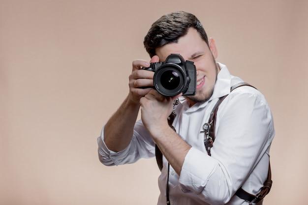 갈색 바탕에 디지털 카메라로 사진을 찍는 사진 작가의 초상화를 닫습니다.