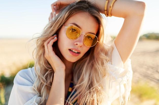 Крупным планом портрет игривой улыбающейся блондинки, играющей с волосами, весело и наслаждаясь летом на пляже.