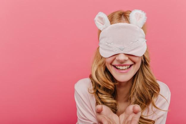 誠実な笑顔でポーズをとってsleepmaskで遊び心のある白人女性のクローズアップの肖像画。写真撮影中に笑っているナイトスーツの熱狂的な女の子。