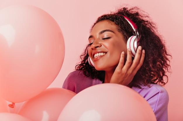 파티를 즐기는 헤드폰에 즐거운 아프리카 여자의 클로즈업 초상화. 생일을 축하하는 동안 기쁜 흑인 여성 듣는 음악.