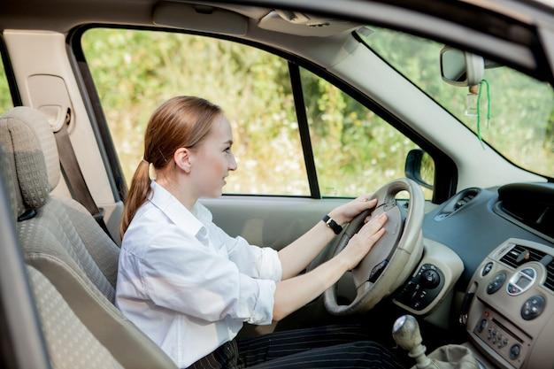 車での忘れられない旅に満足し、嬉しい前向きな表情で気持ちの良い女性の肖像画をクローズアップ、