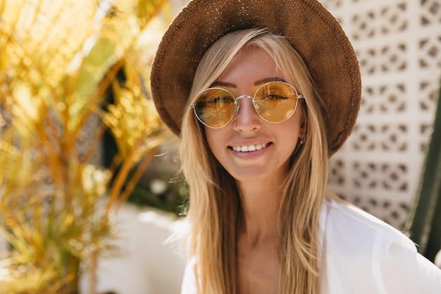 즐거운 백인 여자의 클로즈업 초상화는 우아한 여름 모자를 착용합니다. 휴가를 즐기는 유행 노란색 안경에 긍정적 인 금발 여자의 야외 촬영.