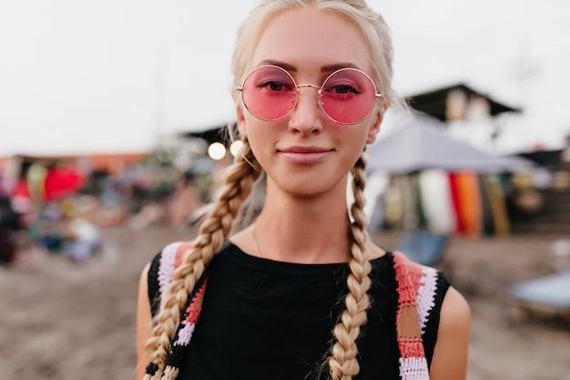 喜んでいる金髪の女性のクローズアップの肖像画は、丸いピンクのサングラスをかけています。